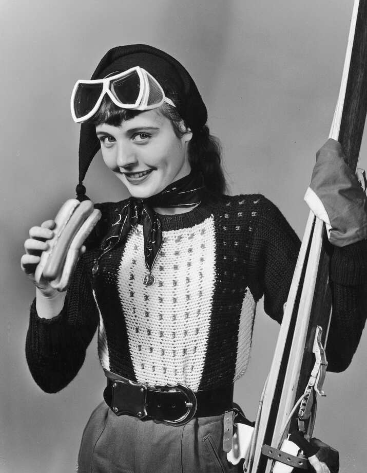 1945:  Studio portrait of a female skier holding a hot dog. She wears a ski cap and goggles and holds a pair of skis in her free hand. Photo: Lambert, Getty Images