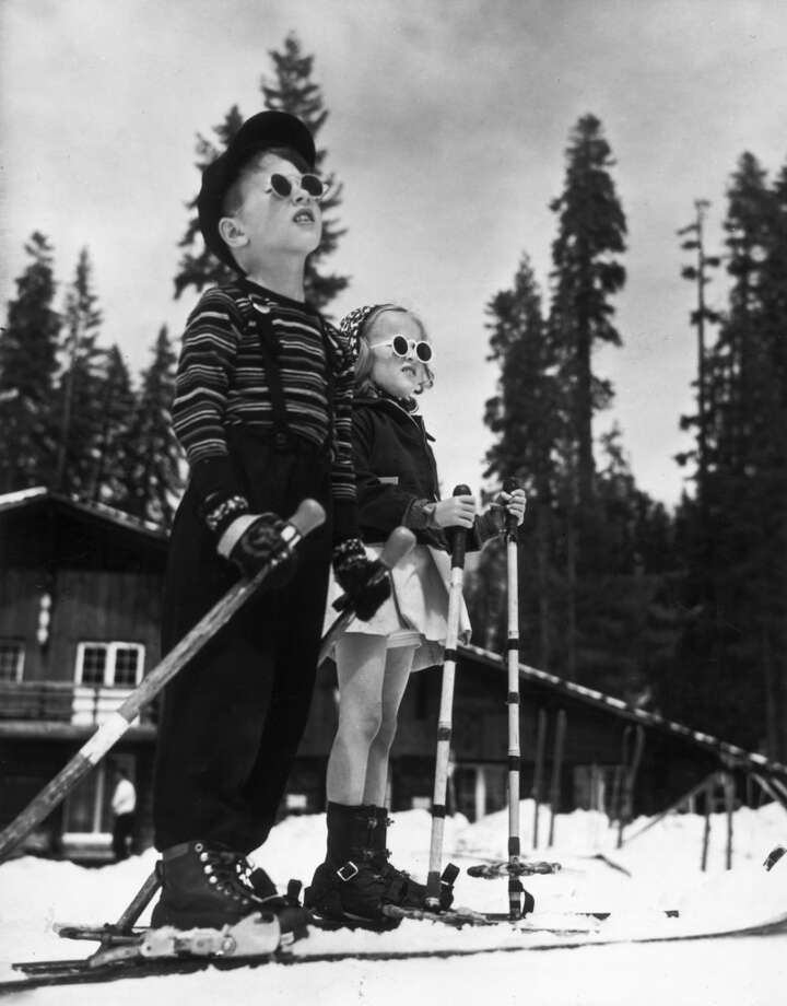 1955:  A boy and a girl standing on skis in the snow in front of a lodge. They hold ski poles and wear sunglasses. The boy wears snowpants and suspenders. Photo: American Stock Archive, Getty Images