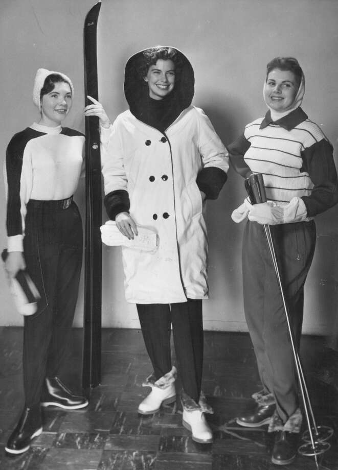 1956: Styles include the knit pullover, black garbardine pants and cap worn (left) by DU Pioneer member, Miss Yvonne temple. the hooded Italian windbreaker (center ) is modeled by Miss Mary Jean Goldsborougth, CWC skier. Miss Pris Wright of DU wears red and white German design with knit helmet wool lined mitts and fur trimmed boots. Photo: Dave Mathias, Denver Post Via Getty Images