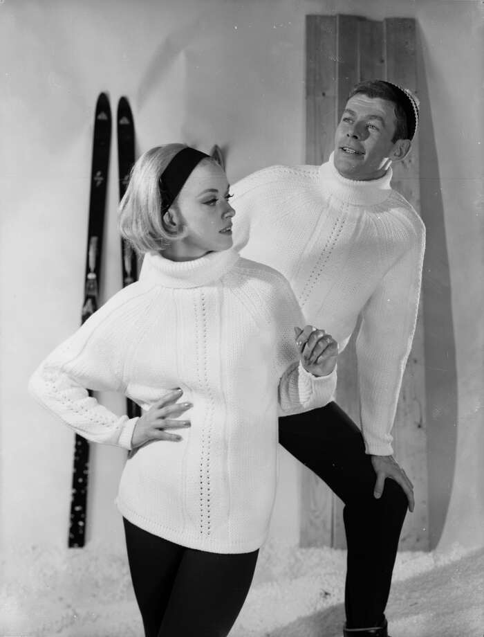 1963:  Two models wearing woolen roll neck sweaters and posing in front of some wall mounted skis. Photo: Chaloner Woods, Getty Images