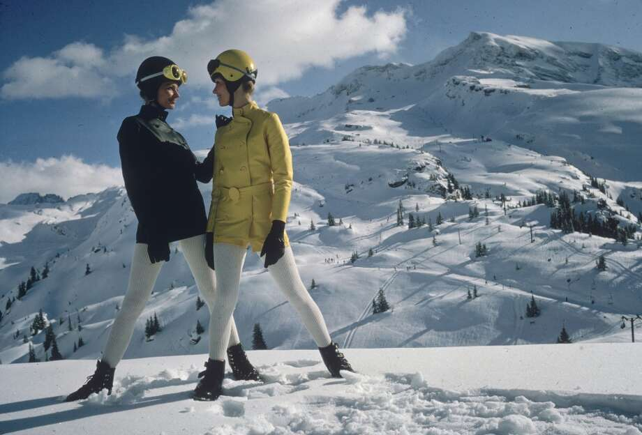 1967:  Two women pose on a mountain in the Alps, wearing ski helmets, coloured jackets and white leggings. Photo: Ernst Haas, Getty Images