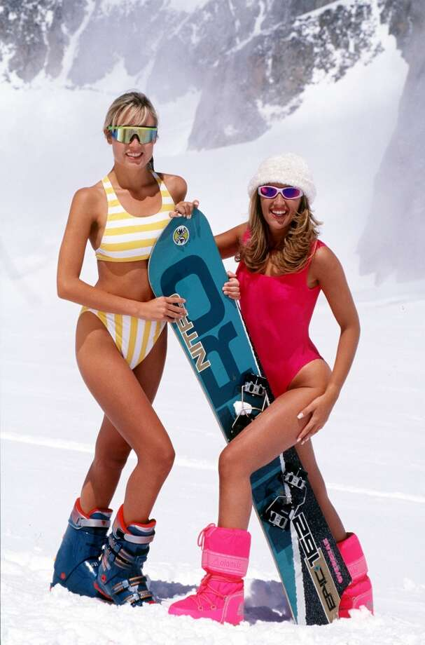 2001: Two women in swimwear, ski boots and sunglasses pose on a snow covered mountain with a snowboard. Photo: Popperfoto, Popperfoto/Getty Images