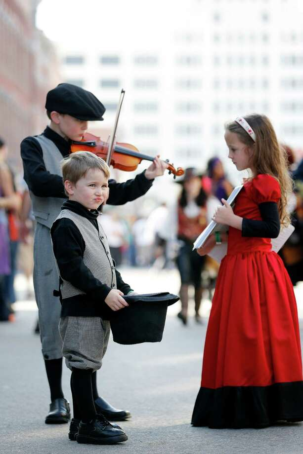 Travis Gibson, 9, rear left, plays the violin as sister, Mary Cathryn, 6, right, displays sheet music with brother, Peter, 4, front holds a hat for donations, Saturday, December 1, 2012 during the annual Dickens on The Strand celebration in Galveston, Texas. (Todd Spoth / For The Chronicle) Photo: TODD SPOTH, Photographer / Todd Spoth