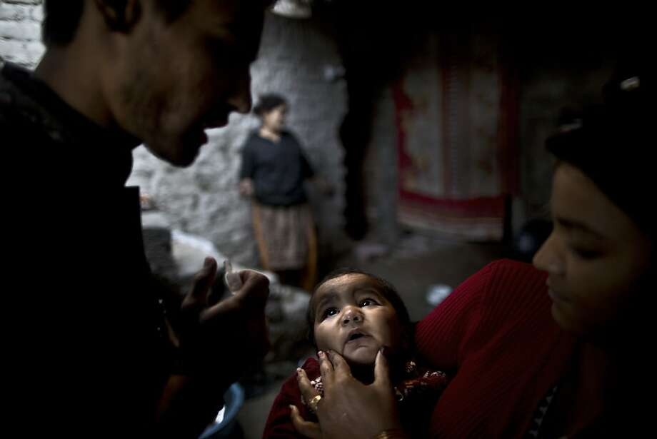 Pakistani Sonya Javed, 20, right, holds her son Shahzeb, 1, to receive a polio vaccine by a health worker at her home in Islamabad, Pakistan, Tuesday, Nov. 26, 2013. Militants have killed over a dozen polio workers and police protecting them over the last year. They claim the health workers are spies and the vaccination is meant to make Muslim children sterile.  Photo: Muhammed Muheisen, Associated Press