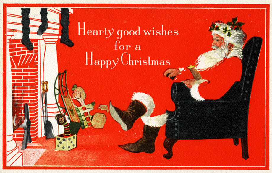 Circa 1910: Greeting card features an illustration of Father Christmas (or Santa Claus) as he sits cross-legged in an armchair before a fireplace, accompanied by the text 'Hearty Good Wishes for a Happy Christmas,' 1910. (Photo by Transcendental Graphics/Getty Images) Photo: Transcendental Graphics, Getty Images / 2007 Getty Images