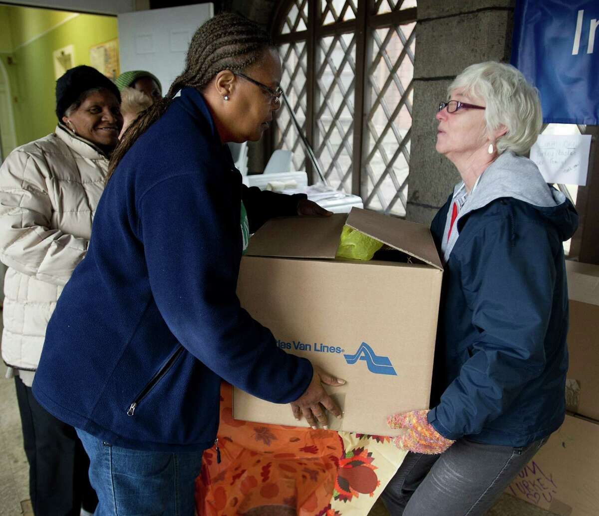 Gloria Dorsey is handed a box of food and a turkey from Cheif Development Officer Holly Lemoine at Inspirica South End Campus as the organization gives Thanksgiving baskets to more than 450 families on Tuesday, November 26, 2013.