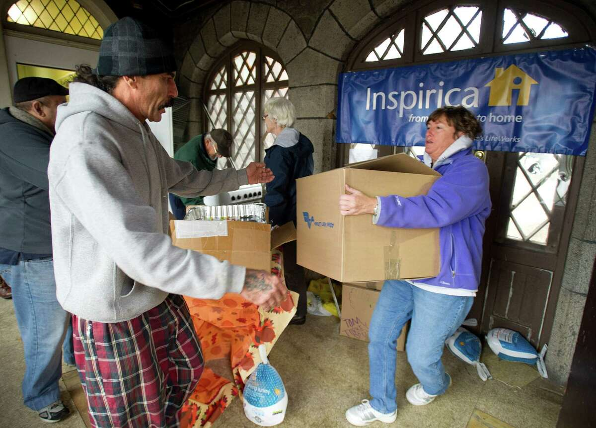 Osvaldo Martin gets a box of food and a turkey at Inspirica South End Campus as the organization gives Thanksgiving baskets to more than 450 families on Tuesday, November 26, 2013.