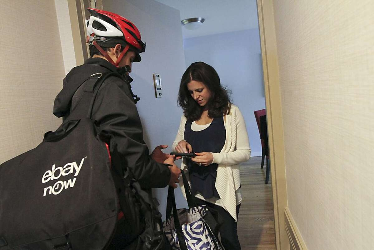 """Fermin Andujar, left, a valet for eBay Now, drops off items for customer Karen Horowitz in New York, Nov. 8, 2013. The app for eBay Now, the company's local shopping service, promises that valets will complete a shop-and-drop-off not just in the same day but """"in about an hour,"""" a timetable crucial to the company's intensifying efforts to one-up Amazon in the delivery game. (Tina Fineberg/The New York Times)"""