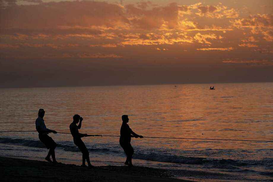 Sunset Strip:Palestinian fishermen pull in their net as the Mediterranean laps at the shore in Gaza City. Photo: Adel Hana, Associated Press