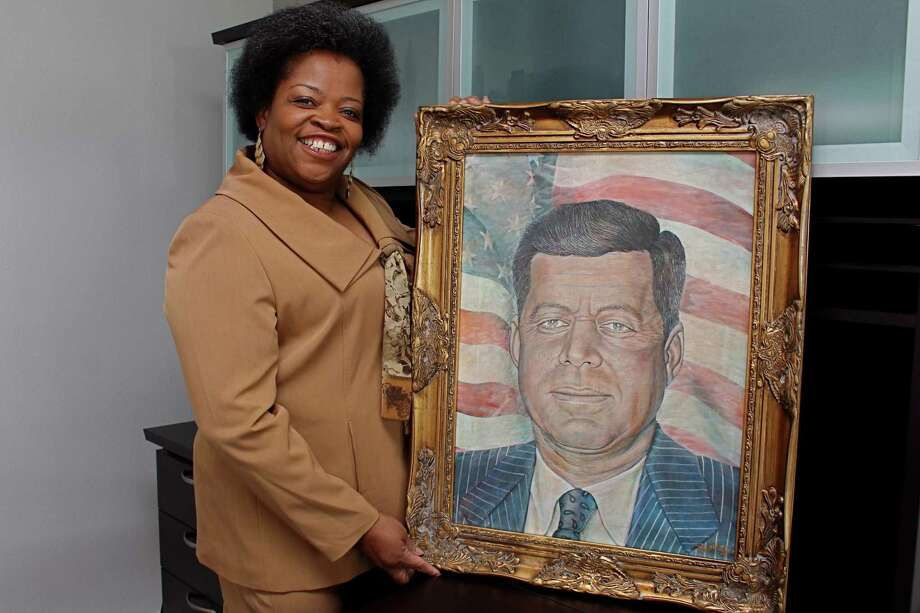Founder and Executive Director of the Honey Brown Hope Foundation Tammie Lang Campbell stands with portrait of President John F. Kennedy by Missouri City based artist Doyle Burley. Photo: Suzanne Rehak, Freelance Photographer