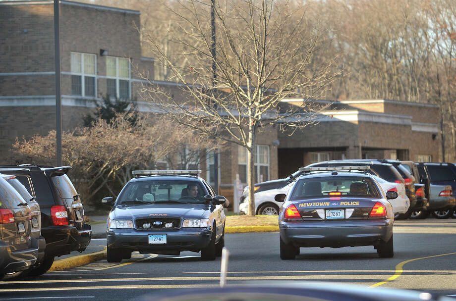 A pair of Newtown police cruisers man the entrance to Hawley School at 29 Church Hill Road in Newtown, Conn. on Monday, November 25, 2013, the day the state's attorney's report of the Sandy Hook Elementary School shootings was released. Photo: Brian A. Pounds / Connecticut Post