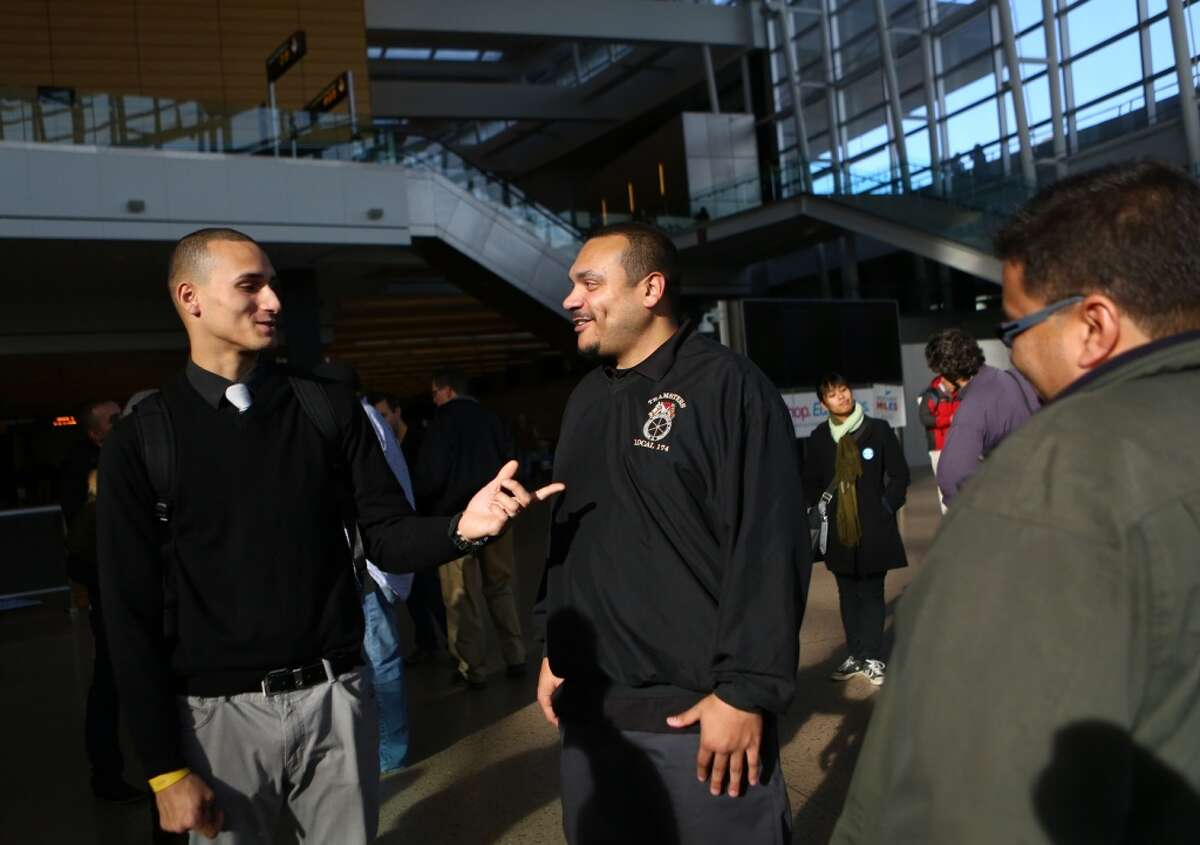 Airport worker Josh Vina, left, thanks union organizers Abraham Taylor and Memo Rivera as supporters of SeaTac's Proposition 1 gather to declare victory on Tuesday, November 26, 2013 at Sea-Tac International Airport. The voter initiative will raise the minimum wage to $15 per hour.