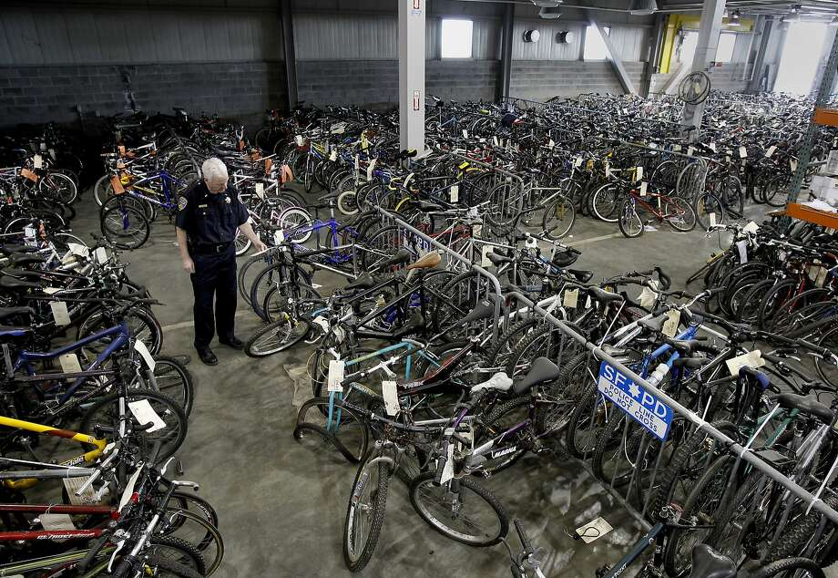 Above, Lt. Joe Cordes looks at an evidence tag on a bicycle at the police storage facility in Hunters Point. Photo: Brant Ward, The Chronicle