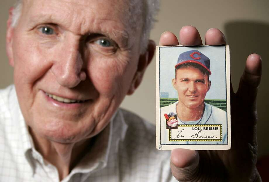 Lou Brissie holds a baseball card at his North Carolina home from his time as a pitcher for the Cleveland Indians. Brissie left for World War II hoping to become a big-league pitcher when he returned and overcame serious war injuries to achieve his goal. Photo: Brett Flashnick, ASSOCIATED PRESS