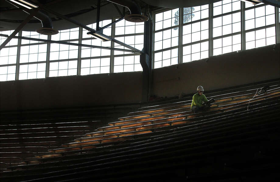 A worker strips clean the wooden benches in the Alamo Convocation Center as construction is still underway at the facility and at Alamo Stadium on Nov. 26, 2013. Photo: Kin Man Hui, San Antonio Express-News / ©2013 San Antonio Express-News