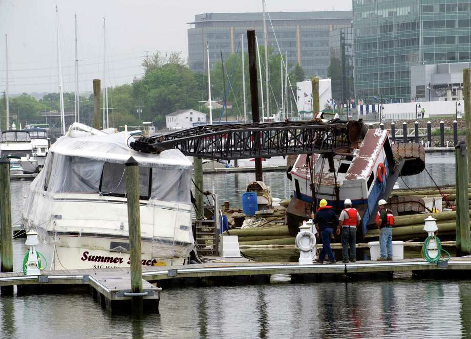 A crane lays collapsed on top of a yacht at Avalon on Stamford Harbor on Wednesday, May 22, 2013. Photo: Lindsay Perry / Stamford Advocate