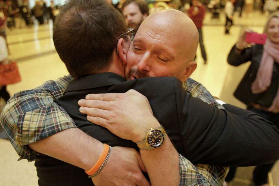Leukemia  survivor Larry Wilson, right, hugs  Johann Beissal, his bone-marrow donor, as  they meet  for the first time at George Bush Intercontinental Airport. Photo: Melissa Phillip, Staff / © 2013  Houston Chronicle
