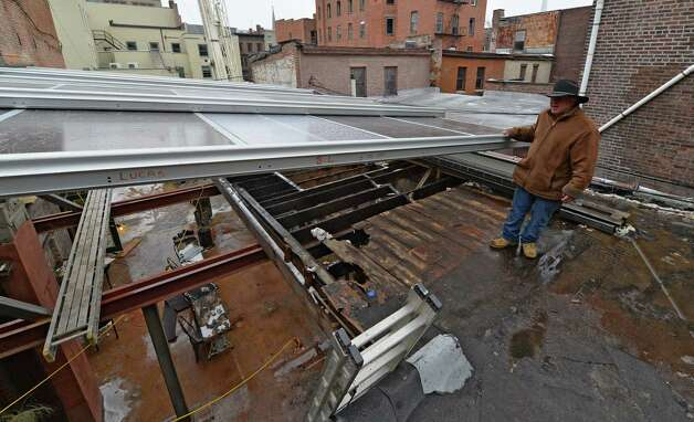 Fabricator Mike Morris of Roll-A-Cover shows how the roof at the Confectionery and Wine Bar will easily open and close Tuesday afternoon Nov. 26, 2013 in Troy, N.Y.    The special roof will give the establishment another year-round room for their patrons.      (Skip Dickstein/Times Union) Photo: SKIP DICKSTEIN / 00024796A