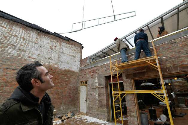 Connecticut-based Roll-A-Cover installed a retractable glass roof over the outdoor garden patio at the Confectionery and Wine Bar in Troy, allowing year-round use.Owner Vic Christopher watches as the last panel goes in place on his new roof at the Confectionery and Wine Bar Tuesday afternoon Nov. 26, 2013 in Troy, N.Y.    The new roof will give the establishment another year-round room for their patrons.      (Skip Dickstein/Times Union) Photo: SKIP DICKSTEIN / 00024796A