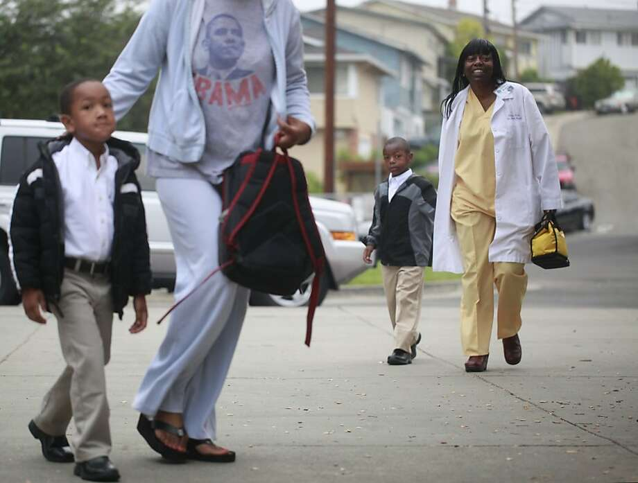 Crighton Dennis, 5, with his mother Makedah Shartukar - followed by Carlton Jr. Perrilliat, 5, and his mother Anastasia Perrilliat walk towards the front doors on the first day of school at The 100 Black Men Community School on Tuesday Sept. 04, 2012 in Oakland, Calif. Photo: Mike Kepka, The Chronicle