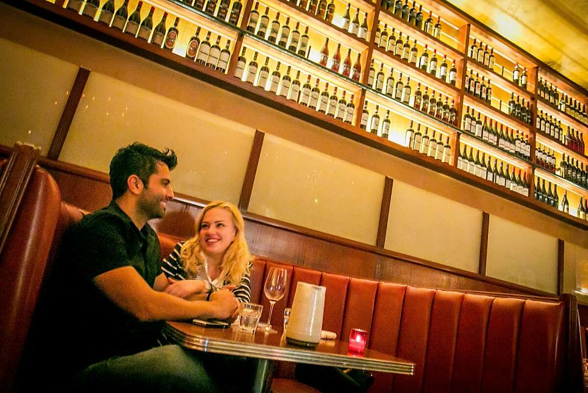 A couple have dinner at Tosca. The booths are still red, but now are leather rather than vinyl.