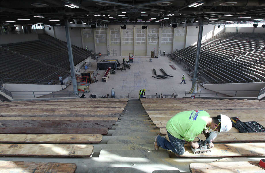 A worker strips bare the wooden benches in the Alamo Convocation Center as construction is still underway at the facility and at Alamo Stadium on Nov. 26, 2013. Photo: Kin Man Hui, San Antonio Express-News / ©2013 San Antonio Express-News