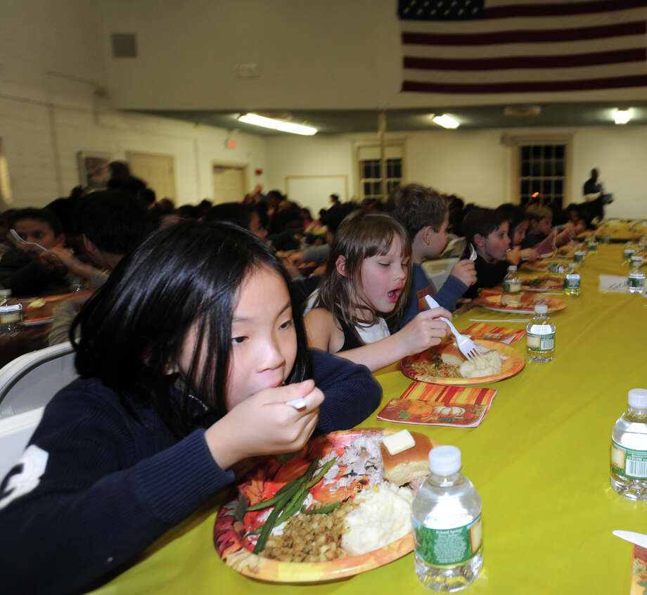 Kwak Yuna, 7, eats her meal during the annual Boys & Girls Club of Greenwich Thanksgiving feast at the club in Greenwich, Tuesday night, Nov. 26, 2013. Takeia McAlister, associate development director of the Boys & Girls Club of Greenwich, said over 400 children were served a Thanksgiving meal by volunteers and club staff and that the meal was sponsored by WatsonâÄôs Catering, Bimbo Bakeries, Credit Suisse, Stew LeonardâÄôs, Smith Party Rentals, Christina Johnson-Wolff and Michael Creamer Landscaping and Lawn Care. Photo: Bob Luckey / Greenwich Time
