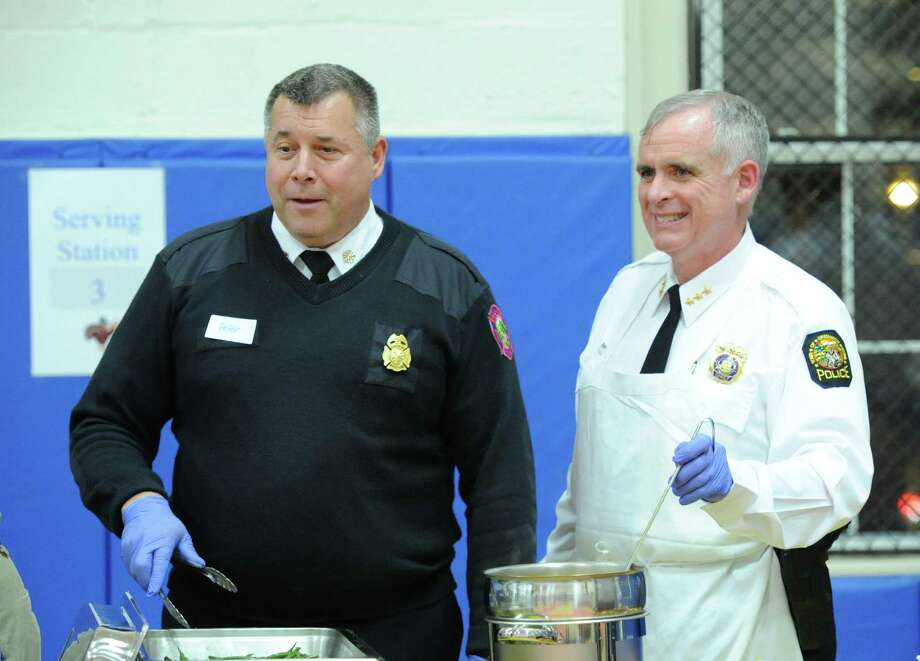 Greenwich Fire Chief, Peter Siecienski, left, and Greeniwch Police Chief, James Heavey, serve food during the annual Boys & Girls Club of Greenwich Thanksgiving feast at the club in Greenwich, Tuesday night, Nov. 26, 2013. Takeia McAlister, associate development director of the Boys & Girls Club of Greenwich, said over 400 children were served a Thanksgiving meal by volunteers and club staff and that the meal was sponsored by WatsonâÄôs Catering, Bimbo Bakeries, Credit Suisse, Stew LeonardâÄôs, Smith Party Rentals, Christina Johnson-Wolff and Michael Creamer Landscaping and Lawn Care. Photo: Bob Luckey / Greenwich Time