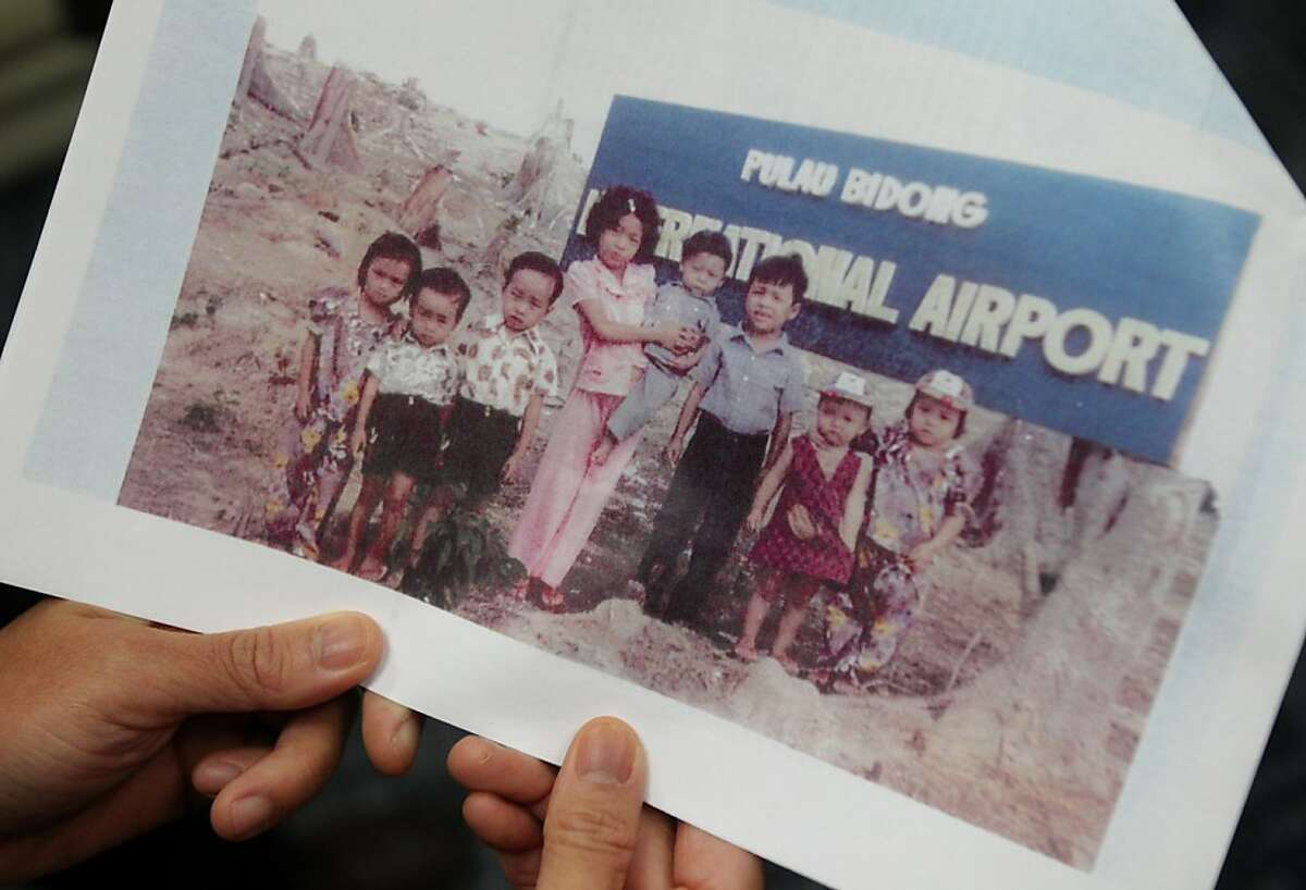 Laura Ly holds a copy of an old photograph taken in 1979 of her two brothers, Hugh, 4, and Michael, 5, second and third from left, with some of their cousins at a Malaysian refugee camp November 26, 2013 at the Sugar Bowl Bakery headquarters in Hayward, Calif. Five Ly brothers immigrated to the United States in the late 70s and early 80s as Vietnamese refugees. Eventually, they all ended up in San Francisco and pooled their money to open up a local coffee shop that also served restaurant food and baked goods. Over the years, they opened multiple shops and then finally expanded to the production-side. They are now one of the largest family-owned businesses in Northern California.