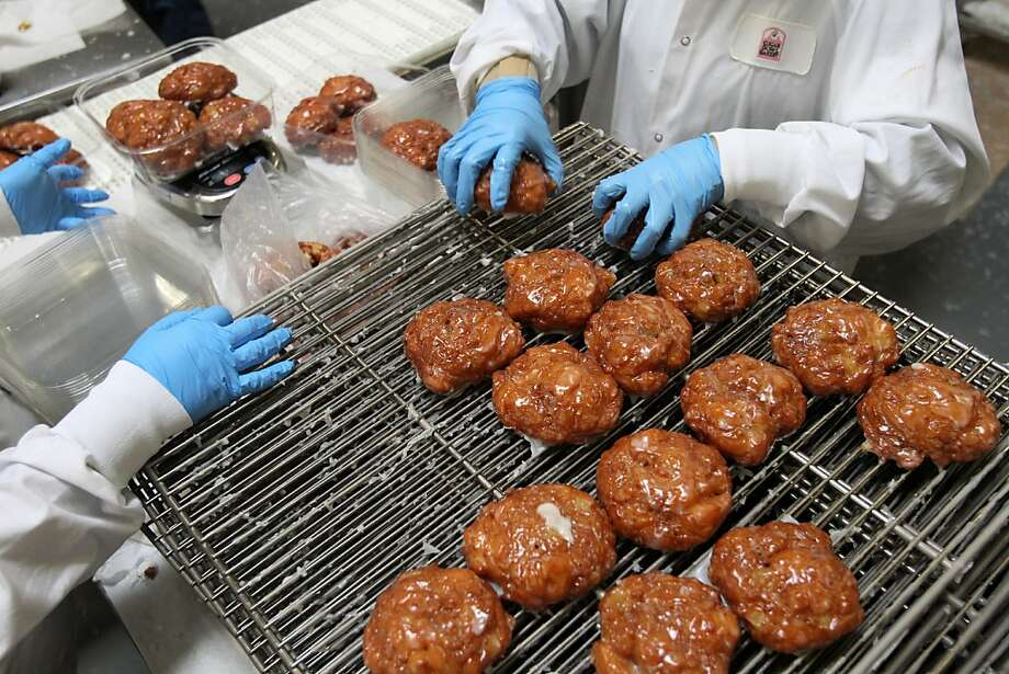 Workers package apple fritters at the Sugar Bowl Bakery plant in Hayward, where the baking production is centralized. Photo: Leah Millis, The Chronicle