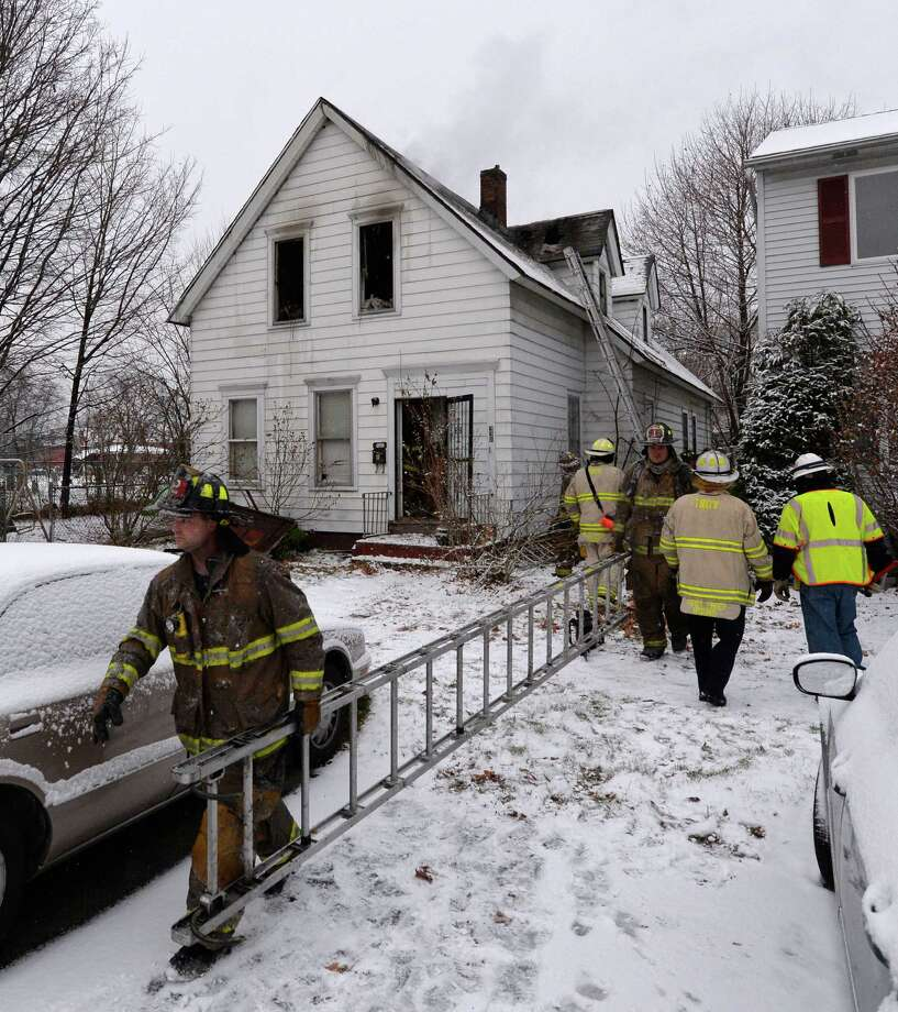 Firefighters start packing up their gear after quickly stopping a fire at 331 Fourth Avenue Tuesday morning Nov. 26, 2013, in Troy, N.Y.       (Skip Dickstein/Times Union) Photo: SKIP DICKSTEIN