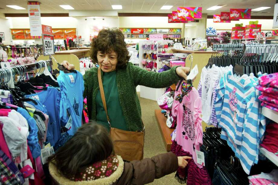 Berta Sosa holds up a pair of outfits for Lindsay Sosa while shopping Tuesday at a Palais Royal store in Missouri City. Shop owners worry that the short selling season this year will drag down profits. Photo: Brett Coomer, Staff / © 2013 Houston Chronicle