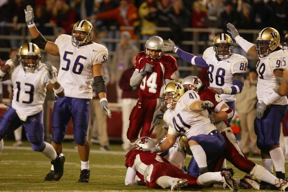 """2002: Washington 29, Washington State 26It took three overtime periods for the unranked Huskies to beat the No. 3 Cougars in one of the most controversial Apple Cups ever. Coach Mike Price's 9-1 Cougs were in line for the Rose Bowl and just had to get past the 6-5 Huskies, but if any game best symbolizes the unpredictably of the Apple Cup, it was this one. The Cougars led 20-10 with 4:30 left, even after backup quarterback Matt Kegel replaced starter Jason Gesser, but WSU """"Coug'd it"""" and allowed the Dawgs to tie it up and send the game to overtime. Washington kicker John Anderson, who had missed his previous three field-goal attempts that day, hit them all during OT as the game went to three extra periods. But the tilt ended in dramatic fashion when the refs ruled that Kegel had thrown a backward pass that Washington defensive end Kai Ellis recovered (pictured). The call was iffy, but the game was over and UW had the 29-26 lead. Things got ugly when Wazzu fans started throwing bottles on the field. Photo: Grant M. Haller, Seattle P-I Archives"""