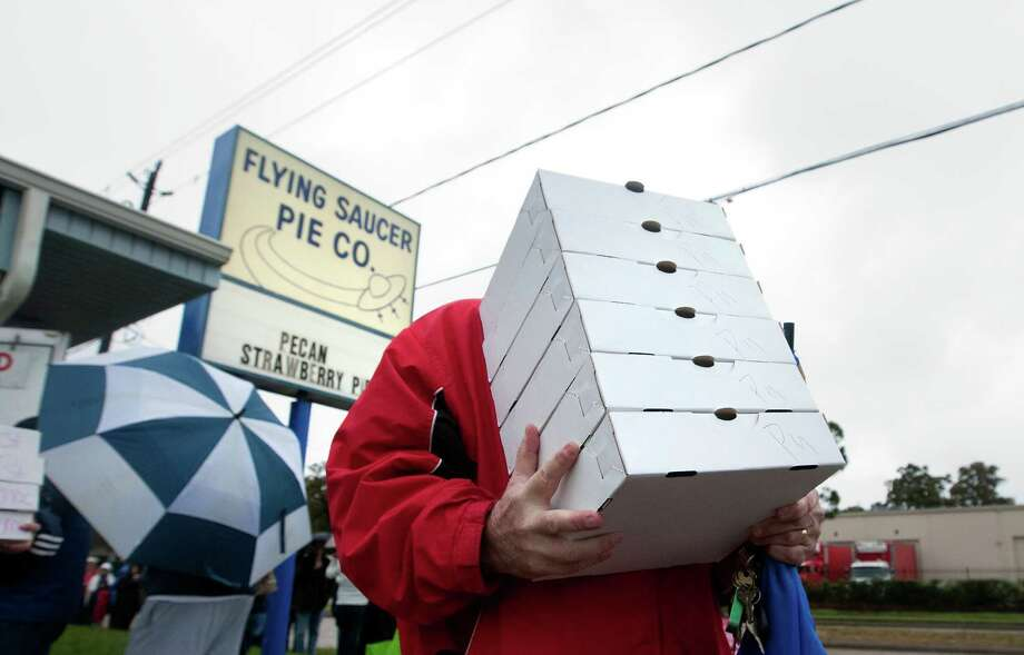 Jeff Qualls carries pies to his truck after purchasing them from Flying Saucer Pie Co., Tuesday, Nov. 26, 2013, in Houston. The P.E. teacher purchased 90 pies on behalf of his principal at Burbank Elementary school, one for each teacher for Thanksgiving. He said that he hopes he gets to choose the pie he wants after hauling them back to the school. Photo: Cody Duty, Houston Chronicle / © 2013 Houston Chronicle