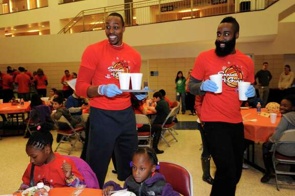 "More than 100 children from the Boys and Girls Clubs, Casa de Esperanza and Kids' Meals were treated to a pre-Thanksgiving dinner at Toyota Center on Tuesday night, with Dwight Howard, left, and James Harden among the players happy to serve as waiters. The evening also included a showing of the movie ""Free Birds,"" which includes a cameo by Howard, on the arena scoreboard."