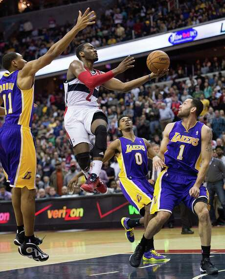 Washington's John Wall, who also had a 360-degree dunk, drives to the basket between the Lakers' Wesley Johnson (11), Nick Young (0) and Jordan Farmar. Photo: Harry E. Walker / McClatchy-Tribune News Service