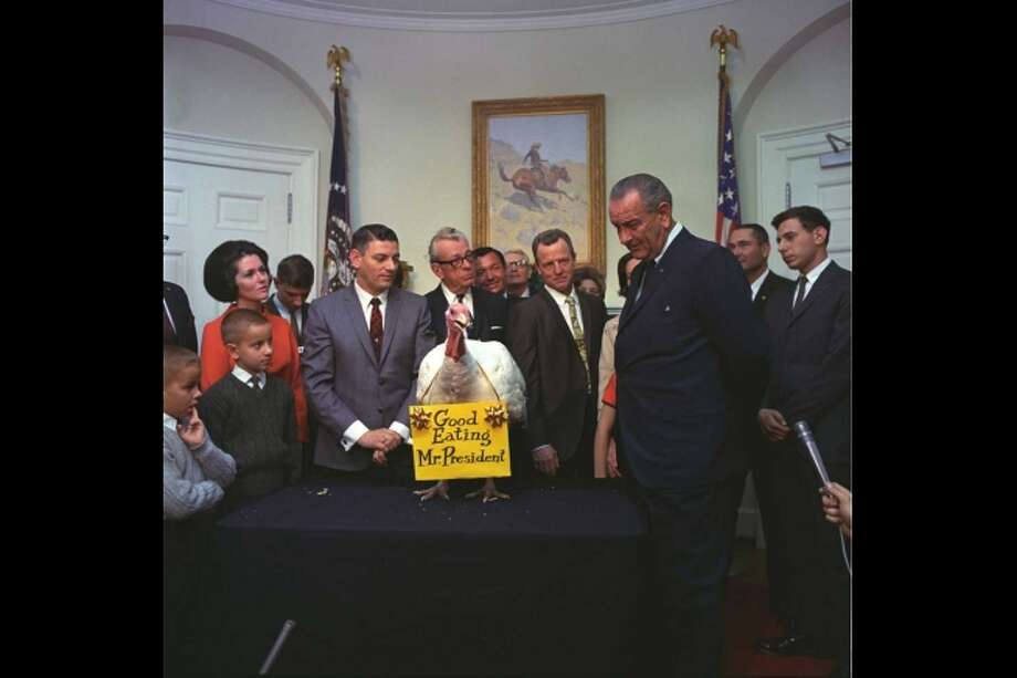 "Annual presentation of the Thanksgiving turkey - Senator Everett Dirksen and representatives from the poultry industry and farm organizations present a turkey to Lyndon B. Johnson in the Fish Room of the White House. The turkey has a sign around its neck that says ""Good Eating Mr. President,"" November 16, 1967. Photo: National Archives And Presidential Libraries"