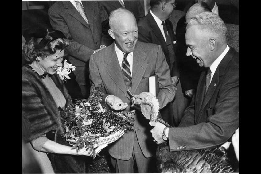 Dwight D. Eisenhower receives a 43-pound turkey from Perry Browning of Winchester, Kentucky, president of the National Turkey Federation. Eisenhower holds the book,