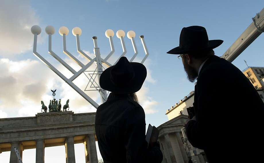 Rabbis Schmuel Segal (L) and Yehuda Teichtal (R) of the Berlin Orthodox Jewish Chabad community look at a giant menorah in front of the Brandenburg Gate in Berlin on November 26, 2013 ahead of Hanukkah. Photo: John Macdougall, AFP/Getty Images