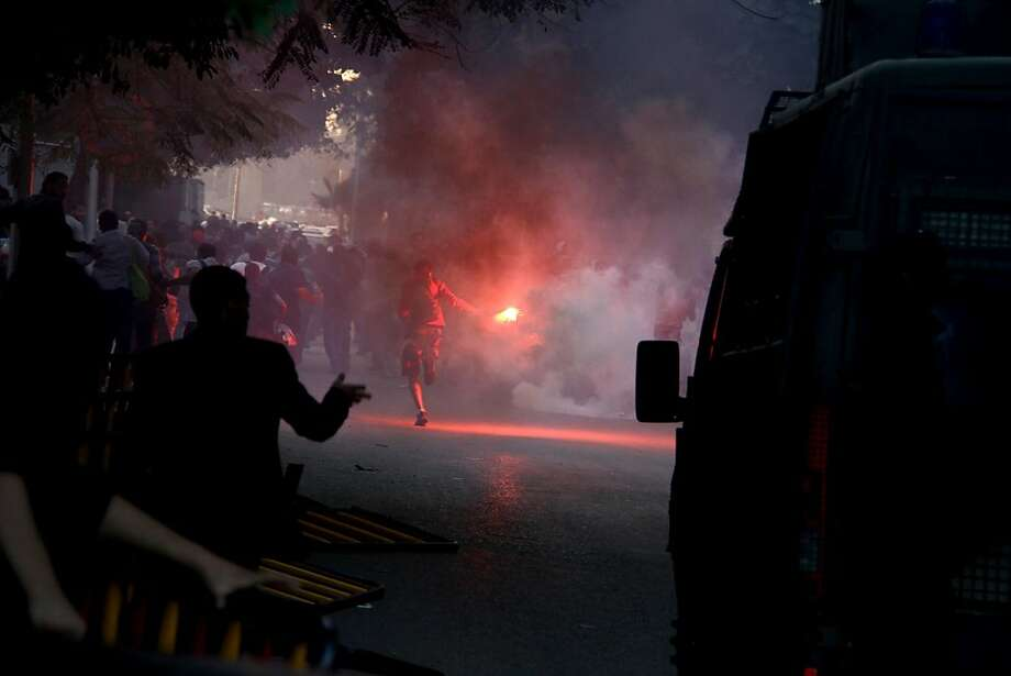 Am anti-government activist runs with a flare in Cairo, Tuesday, Nov. 26, 2013 as police disperse a protest, the security forces' first implementation of a controversial new law forbidding protests held without a permit from authorities. Photo: Ahmed Gomaa, Associated Press