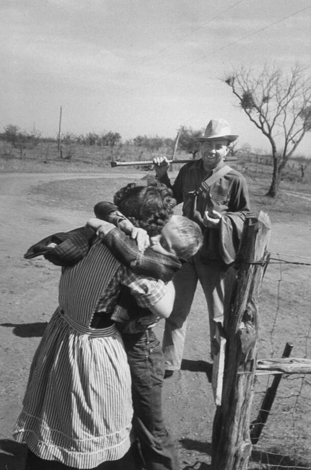 Author Fred Gipson with his son Mike who is hugging his mother after coming home from coon hunt, 1949. Photo: Thomas D. McAvoy, Time & Life Pictures/Getty Image