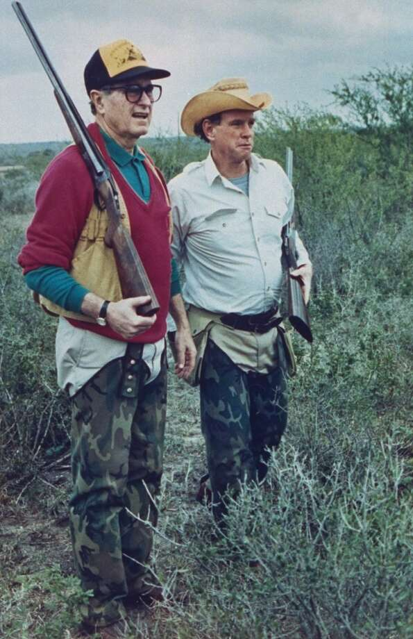 US Pres. George Bush dressed in hunting gear w. friend/oil heir William Farish, both sporting rifles, on quail hunt at Lazy F ranch, 1989. Photo: David Valdez, Time & Life Pictures/Getty Image