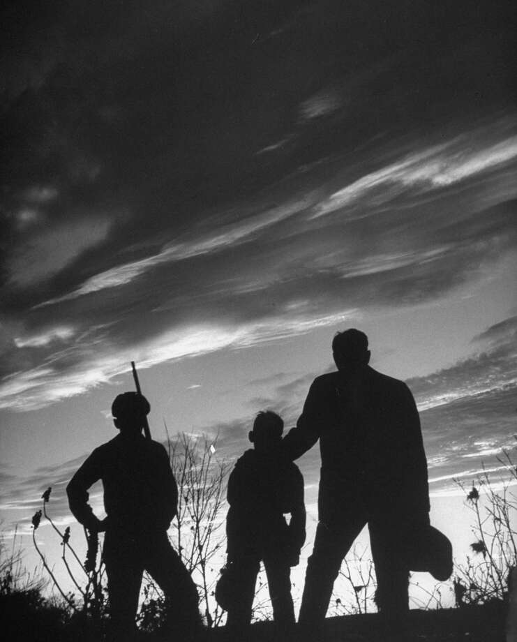 Author Fred Gipson with his son Mike and another boy looking at sunset before coon hunt, 1949. Photo: Thomas D. McAvoy, Time & Life Pictures/Getty Image