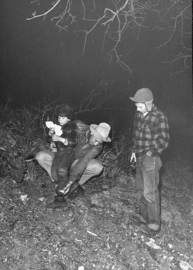 Author Fred Gipson with his son Mike who was bitten twice during coon hunt, sniffling as his father looks at his leg, 1949. Photo: Thomas D. McAvoy, Time & Life Pictures/Getty Image