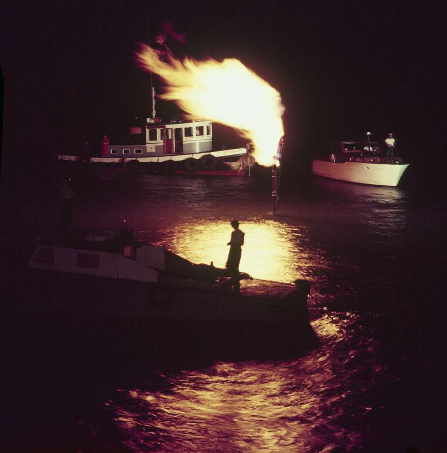 Oil workers fishing trout by light of oil flare at Shamrock Cove in the Gulf of Mexico in 1954. Photo: John Dominis, Time & Life Pictures/Getty Image