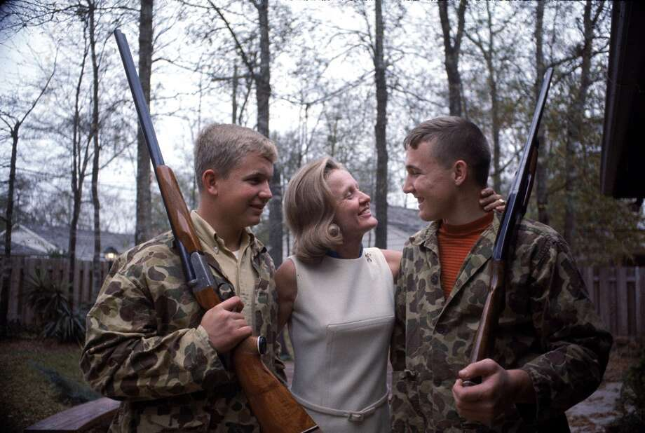 Sue Borman hugs her sons Fred and Ed, both of whom wear camouflage jackets and hold hunting rifles, Houston, Texas, December 1968. The boys' father, and Sue's husband, is Apollo 8 astronaut Frank Borman. Photo: Lynn Pelham, Time & Life Pictures/Getty Image