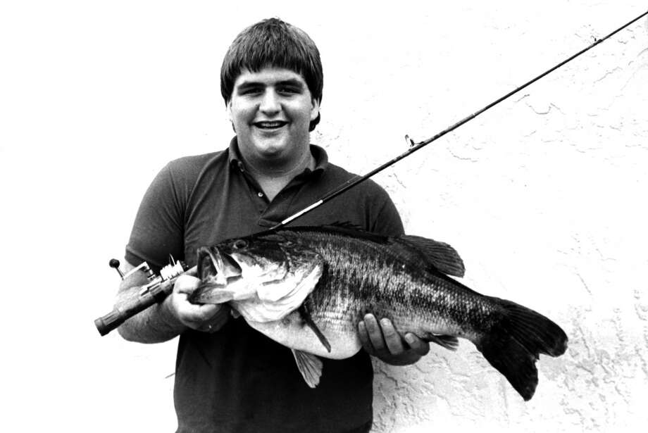 A boy stands holding a fishing rod and a 12 pound 6 ounce largemouth bass he caught on August 19, 1983 in San Augustine County, Texas Photo: IGFA, Getty Images