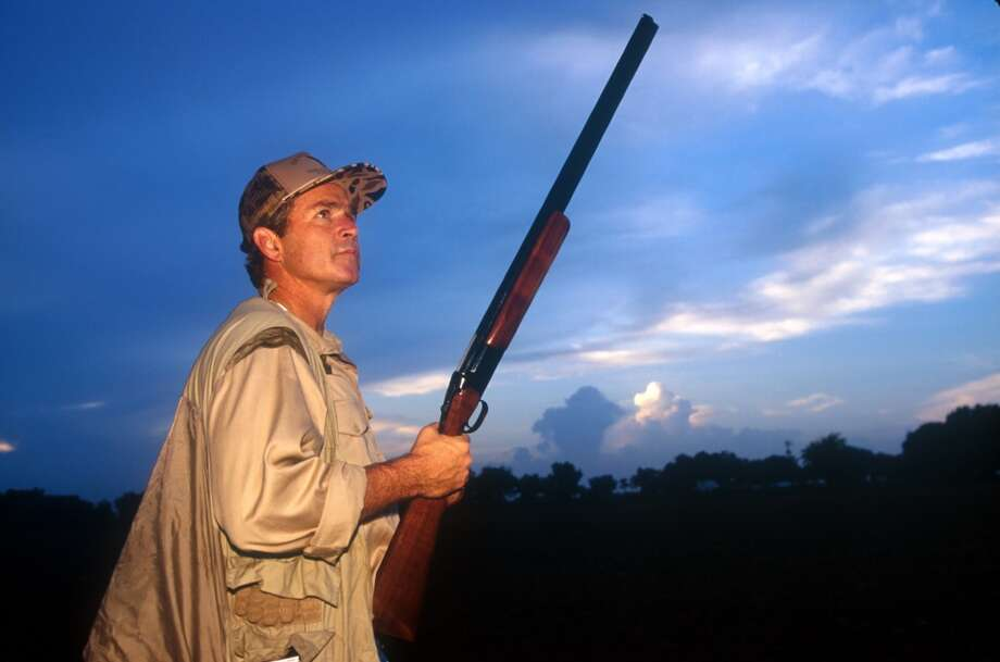 Texas Governor George W. Bush looks up at the sky for an opportunity on the first day of Dove hunting season in Hockley, Texas, September 1, 1994. Photo: Paul S. Howell, Getty Images