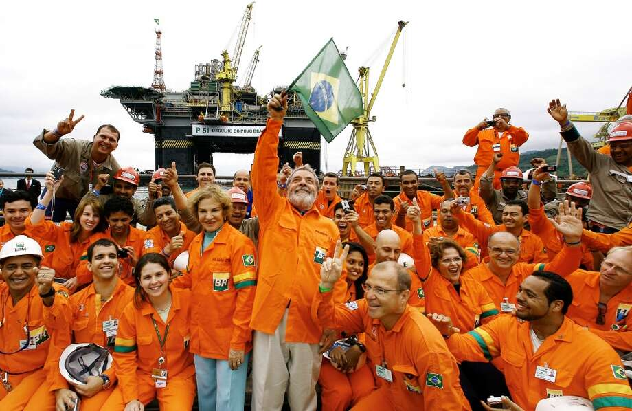 13. Petróleo Brasileiro S.A. (Petrobras) -- semi-public oil company of Brazil  2012 rank -- 15  [Photo: Then-Brazil President Luiz Inacio Lula da Silva (center) waves a national flag next to his wife Marisa Leticia, while posing for a picture with workers of the Brasil-Fels shipyard who built the Petrobras oil platform P-51 in 2008.] Photo: HO, AFP/Getty Images