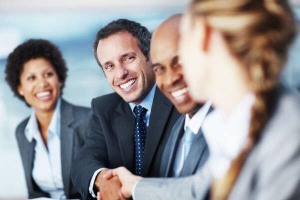 Mature boss congratulating an employee during a meeting
